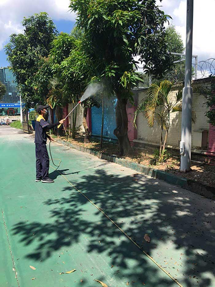 永盛技术人员正在对学校中的树木进行病媒消杀施工现场图